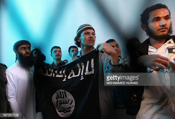 Yemeni AlQaeda militants hold a black AlQaeda flag as the judge sentenced them to jail for plotting attacks in Yemen at the court in Sanaa on April...