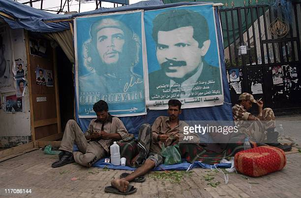 Yemeni antigovernment protesters chew qat a mild natural narcotic as they sit undeneath a poster of Cuban revolutionary Che Guevara and Yemeni former...