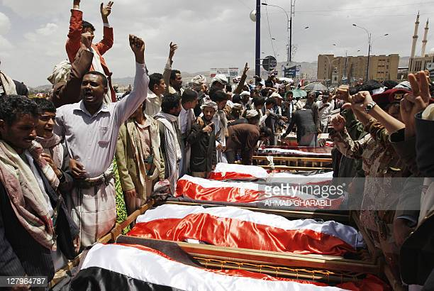 Yemeni antiregime activists shout slogans next to the coffins of fighters loyal to opposition tribal chief Sheikh Sadiq alAhmar during a mass funeral...