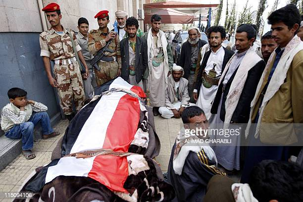 Yemeni antiregime mourners gather next to the coffin of fighter loyal to opposition tribal chief Sheikh Sadiq alAhmar during a mass funeral in Sanaa...