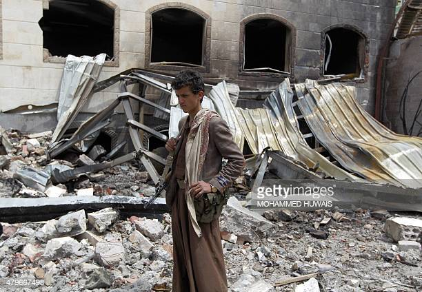 A Yemeni armed young man stands amidst the debris of a house destroyed in an airstrike by the Saudiled coalition in the capital Sanaa on July 6 2015...