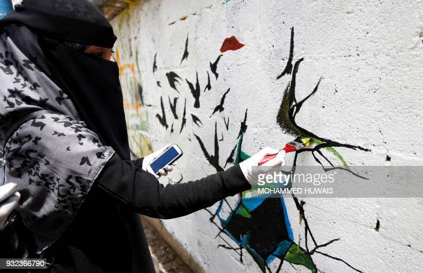 Yemeni artist paints graffiti on a wall during a campaign called 'Open Day of Art' in support of peace in the war-affected country, in the capital...