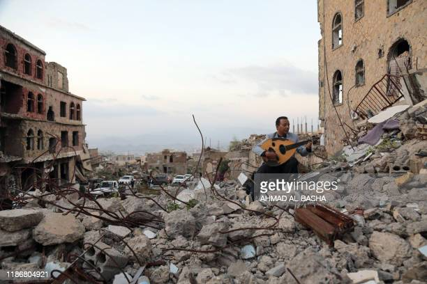 Yemeni artist sitting atop the rubble of a collapsed buiding, plays the aoud during a street performance in Yemen's third city of Taez, on December...