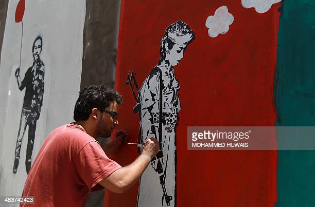 A Yemeni artist works on a mural as part of a campaign to end the recruitment of child soldiers by tribal militias on April 10 2014 in the capital...