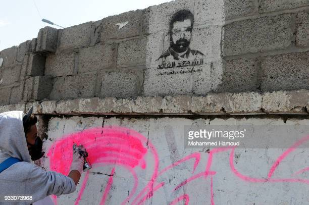 """Yemeni artist writes the word """"PEACE"""" on a wall under a picture of the Houthi 1-leader Housin al-Houthi, during an Open Day of graffiti campaign call..."""