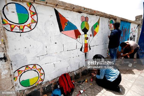 Yemeni artists paint graffiti on a wall during a campaign called 'Open Day of Art' in support of peace in the war-affected country, in the capital...