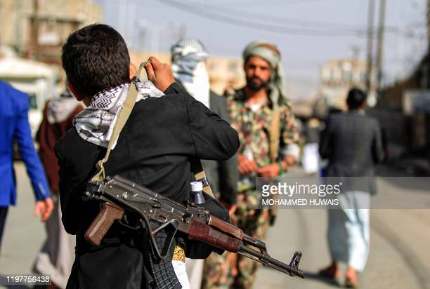 A Yemeni boy adjusts on his shoulder the strap of a Kalashnikov assault rifle as he attends a demonstration in the Huthi rebelheld capital Sanaa on...