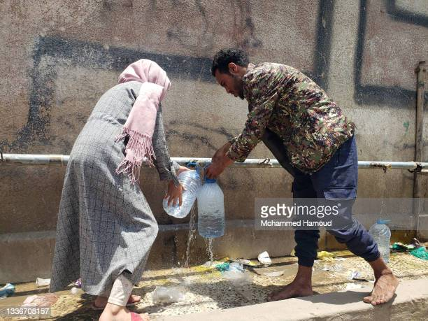 Yemeni boy and a girl collect clean water provided by a charitable group amid a severe water crisis on August 27, 2021 in Sana'a, Yemen. In war-torn...