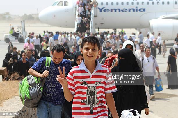 A Yemeni boy flashes the sign for victory after arriving at the airport in the southern city of Aden on August 6 2015 on the first civilian aircraft...