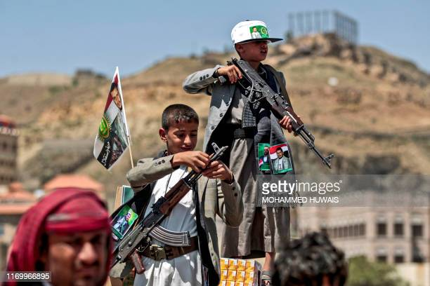 Yemeni boy lines up a round of ammunition atop the barrel of a Kalashnikov assault rifle with a flag sticking from his jacket showing a picture of...