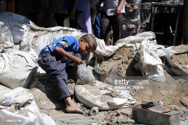 Yemeni boy looks for bullet casings, to sell as scrap metal, in a street in an old market on April 27 in Yemen's third city of Taiz after clashes...