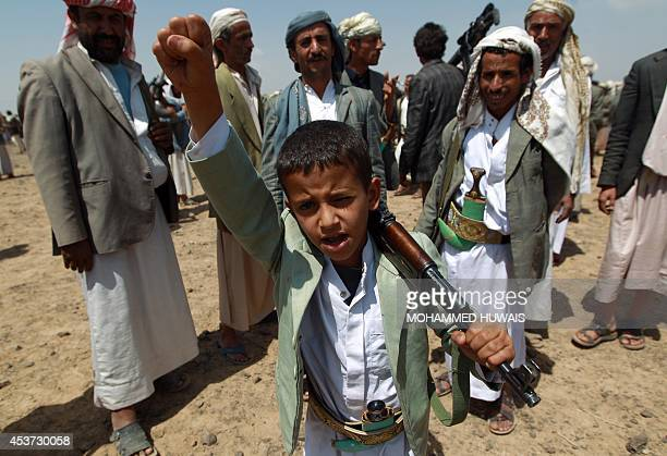 A Yemeni boy loyal to the Shiite Huthi movement holds his gun during a tribal gathering against alQaeda militants in the Bani alHarith area north of...