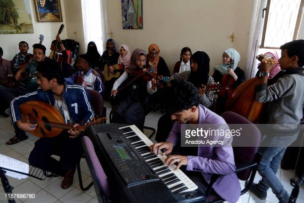 Yemeni boy play the piano as another holds an oud in a music class at a cultural center in Sana'a Yemen on July 25 2019 Yemeni youth take music...