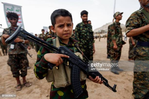 Yemeni boy poses with a Kalashnikov assault rifle during a gathering of newly-recruited Huthi fighters in the capital Sanaa, to mobilize more...