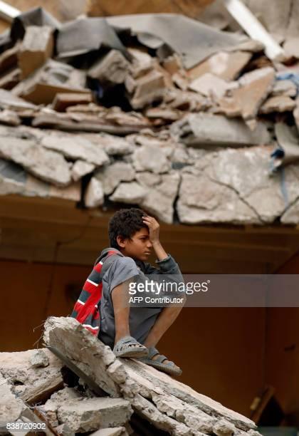 A Yemeni boy reacts as he sits on the debris of a house hit in an air strike in the residential southern Faj Attan district of the capital Sanaa on...
