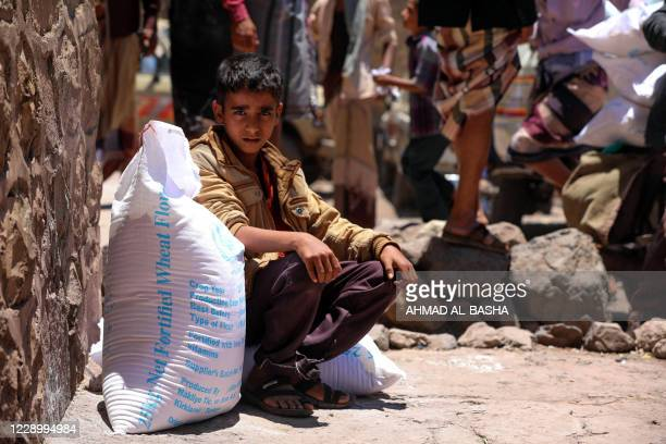 Yemeni boy receives humanitarian aid, donated by the World Food Programme , in the country's third city of Taez, on October 10, 2020. - Yemen's Huthi...