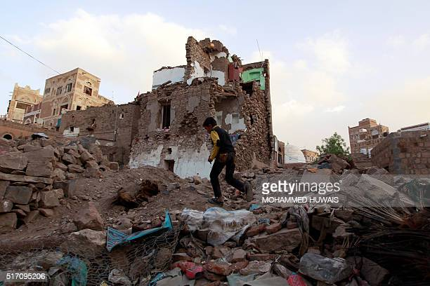 Yemeni boy runs on March 23 2016 past buildings that were damaged by air strikes carried out by the Saudiled coalition over the past year in the...