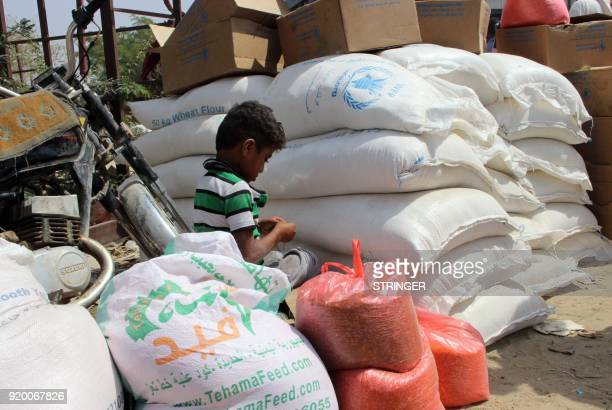 A Yemeni boy sits amidst bags of food aid in the northern district of Abs in Yemen's Hajjah province on February 18 2018 / AFP PHOTO / STRINGER