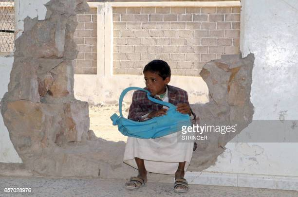 A Yemeni boy sits in a hole in a wall at a school that was damaged in the country's ongoing conflict between the Saudiled Arab coalition fighting...