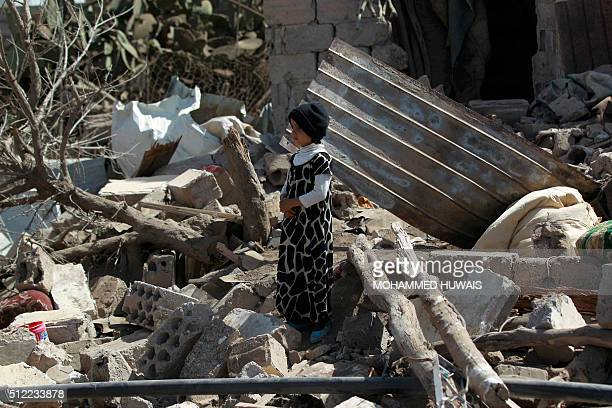 Yemeni boy stands in the rubble of buildings destroyed in an airstrike by the Saudiled coalition on February 25 2016 in the capital Sanaa / AFP /...