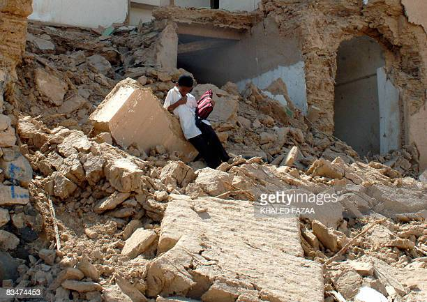 A Yemeni boy stands on the rubble of his collapsed home in the historical city of Shibam in Hadramaut province of eastern Yemen on October 28 2008...