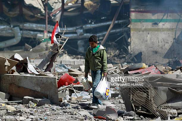 Yemeni boy walks amid the ruins of a school and a bowling club hit by an airstrike carried out by the Saudiled coalition in the capital Sanaa on...