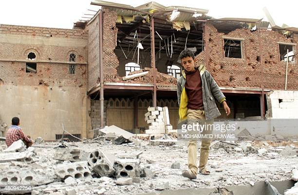 A Yemeni boy walks amid the ruins of buildings destroyed in an airstrike by the Saudiled coalition on the capital Sanaa on July 16 2015 Loyalist...