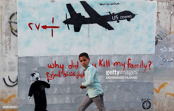 A Yemeni boy walks past a mural depicting a US drone and reading ' Why did you kill my family' on December 13 2013 in the capital Sanaa A drone...