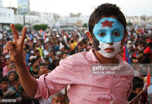 A Yemeni boy with his face painted in the colours of southern separatist movement's flag flashes the Vsign in the southern city of Aden on November...
