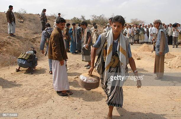 A Yemeni carries a landmine during the opening of a road in Saada north of Sanaa on February 15 following a truce between rebels and government...