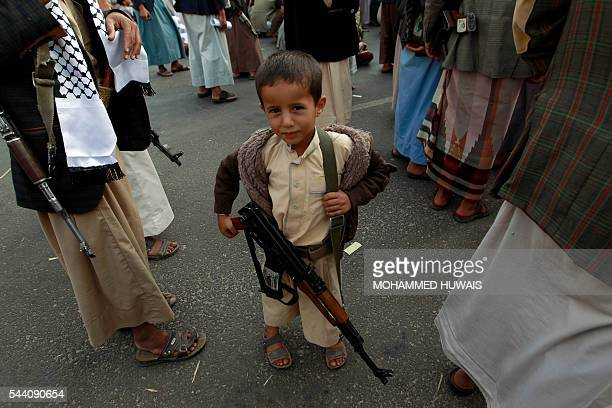 A Yemeni child carries a weapon during a rally gathering supporters of the Shiite Huthi movement to mark the Quds International day in support of...