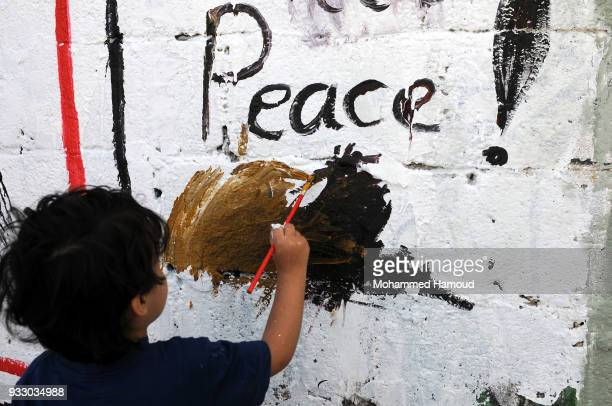 Yemeni child draws as he takes part in an Open Day of graffiti campaign call for peace on March 15, 2018 in Sana'a, Yemen.