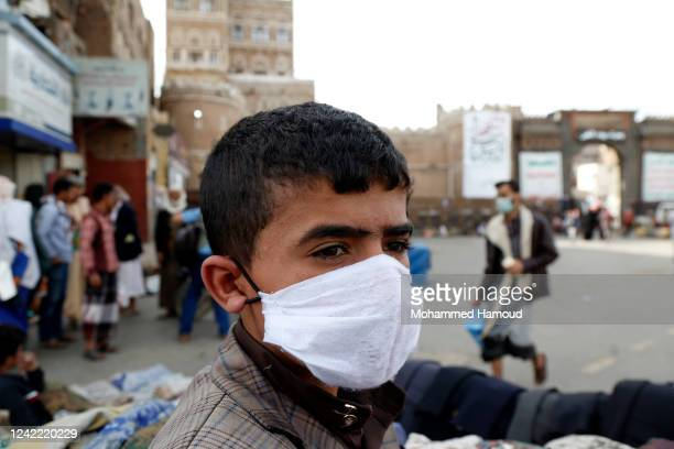 Yemeni child in a protective face mask does shopping during the fears of the COVID-19 spread, at a popular market on June 02, 2020 in Sana'a, Yemen.