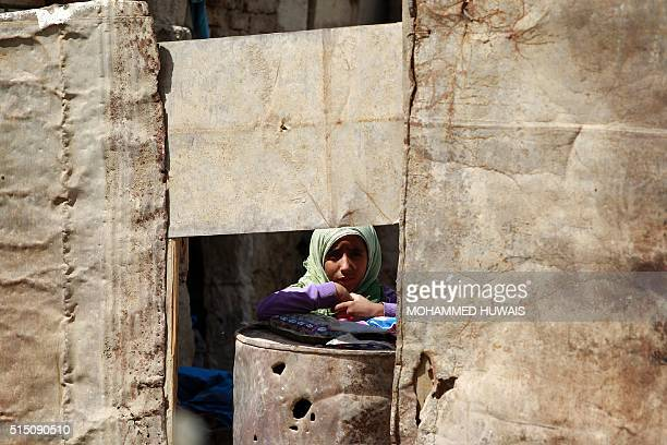 A Yemeni child stands inside her house which was damaged several months ago in an airstrike by the Saudiled coalition on March 12 in the capital...