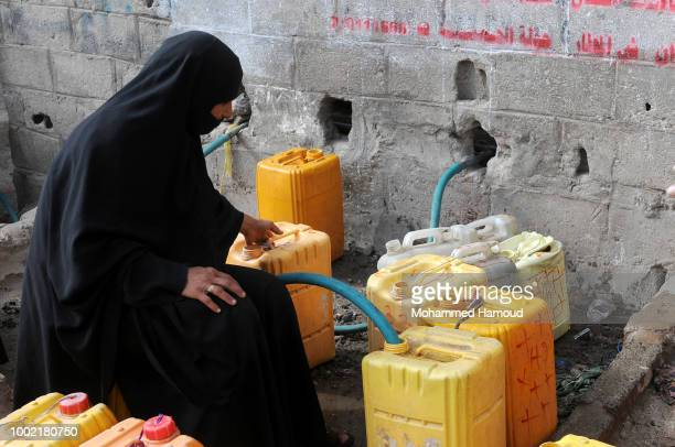 Yemeni child waits to fill his water bottles with clean water provided by charity groups during an ongoing water crisis on July 17 2018 in Sana'a...