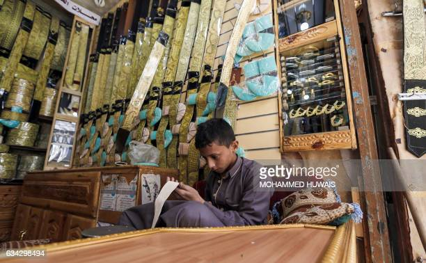 A Yemeni child works in a shop selling 'janbiyas' traditionallyworn short curved daggers in Sanaa's Suq AlMelh on January 24 2017 The devastating...