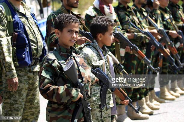 Yemeni children accompanied by their fathers hold weapons during a gathering in Sanaa to show support for the Huthi Shiite movement against the...