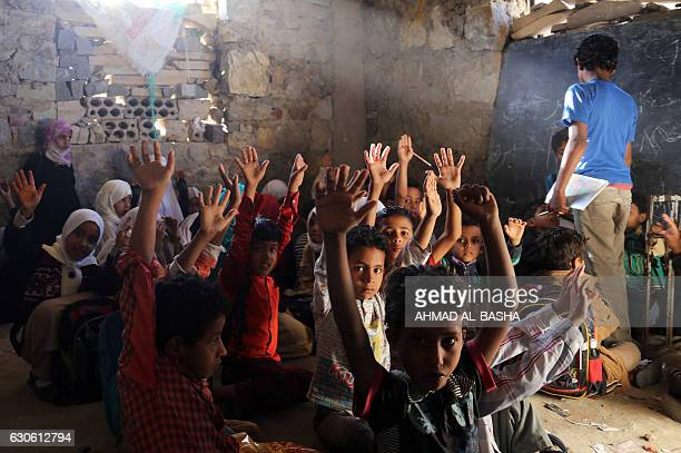 TOPSHOT Yemeni children attend a class on December 27 at a school that was damaged in a recent Saudiled air strike in the country's thirdcity of Taez...