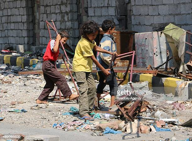 Yemeni children collect iron from the debris of the buildings after the clashes between the Houthi Ansarullah movement members and the people's...