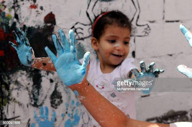 Yemeni children cover theur arm with colors during an Open Day of graffiti campaign call for peace on March 15, 2018 in Sana'a, Yemen.
