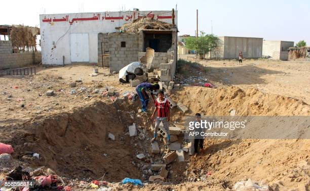 Yemeni children gather at a crater left at the site of a reported air strike by the Saudiled coalition against a health centre in the area of Abbas...