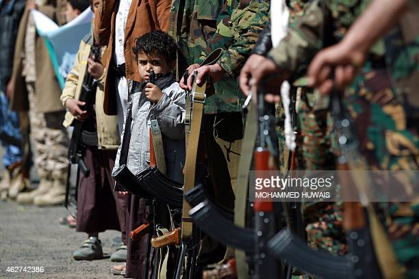 Yemeni children hold automatic rifles as they join grown up relatives in a tribal gathering organised by the Shiite Huthi movement in Sanaa on...
