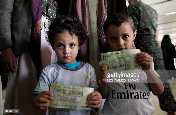 Yemeni children hold bank notes as they queue up at a post office in Sanaa to donate money to the rebelcontrolled Central Bank of Yemen on September...