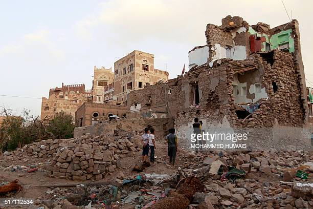 Yemeni children look on March 23 2016 at buildings that were damaged by air strikes carried out by the Saudiled coalition over the past year in the...