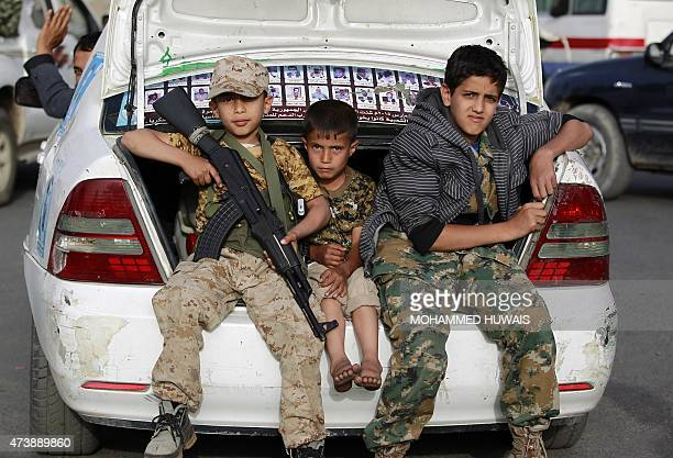 Yemeni children one holding a weapon sit in a car boot during a march of supporters of the Shiite Huthi movement in the capital Sanaa in protest to...