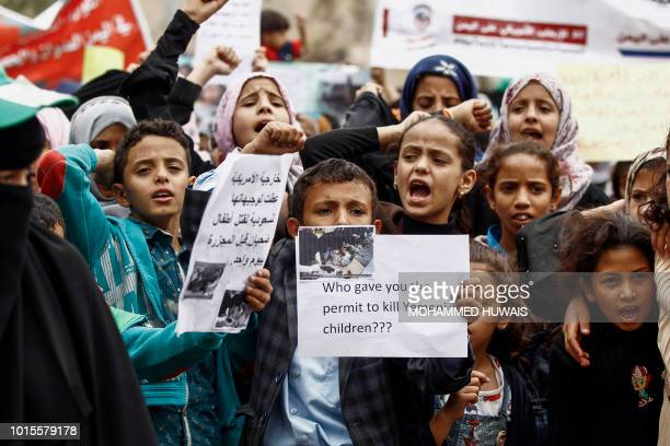 Yemeni children raise protest signs and chant slogans during a demonstration in the capital Sanaa on August 12 against an air strike by the Saudiled...