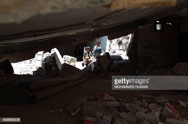 Yemeni children sit amid the debris of their house after it was damaged during fighting between Shiite Huthi rebels and government forces in the...