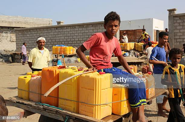 Yemeni children stand amid empty jerrycans as they wait to fill them with water from a donated source amid ongoing widespread disruption of water...