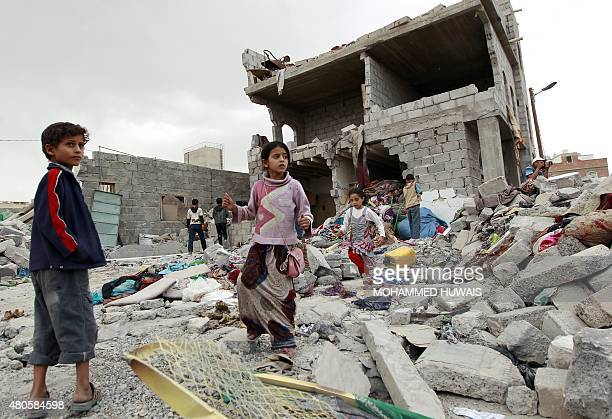 Yemeni children stand amid the rubble of a building damaged in an airstrike by the Saudiled coalition on the capital Sanaa on July 13 2015 Air...