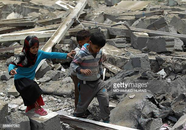 Yemeni children walk amidst the rubble of a house in Yemen's Huthi rebelheld capital Sanaa on August 11 after it was reportedly hit by a Saudiled...
